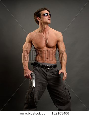 The strong muscle man is holding a pistol.