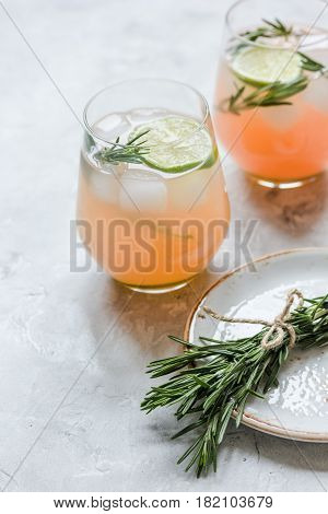 healthy morning with fresh drink, sliced lime and rosemary on stone table background