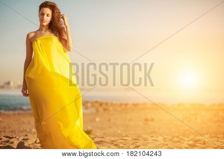 Fashion girl in a long dress against a summer sunset background. A beautiful model on the beach sand near the water in a dress flying in the wind. Luxurious sexy woman