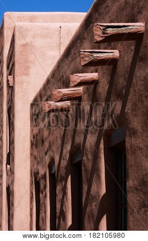 Vigas in Santa Fe, Mexico cast shadows across the adobe facades of the downtown buildings