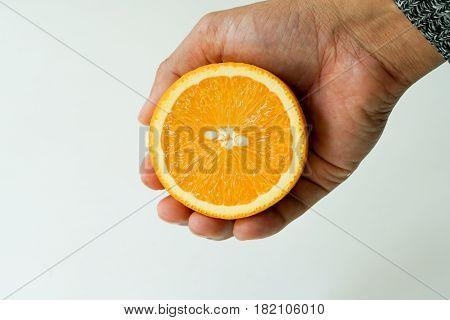 Slice organic orange holding on the hand