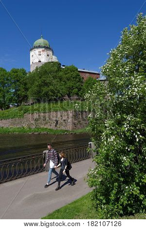 VYBORG, LENINGRAD OBLAST, RUSSIA - JUNE 6, 2015: People on the embankment against the tower of St. Olav of Vyborg Castle. The castle was founded in 1293