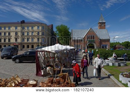 VYBORG, LENINGRAD OBLAST, RUSSIA - JUNE 6, 2015: People at the market square. The market building was erected in 1904-1904 by design of Karl Segerstad