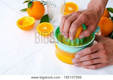 Freshly squeezed orange juice by men's hands, in turquoise juicer on white background, horizontal, copy space