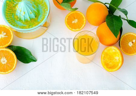 Freshly squeezed orange juice in turquoise juicer on white background, horizontal, top view