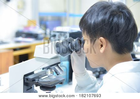 Young scientist looking through a microscope in a laboratory.