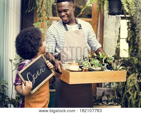 Man Carrying Plants Standing With Son Showing Open Sign