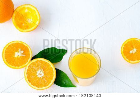 Freshly squeezed orange juice in glass on white background, horizontal, top view, copy space