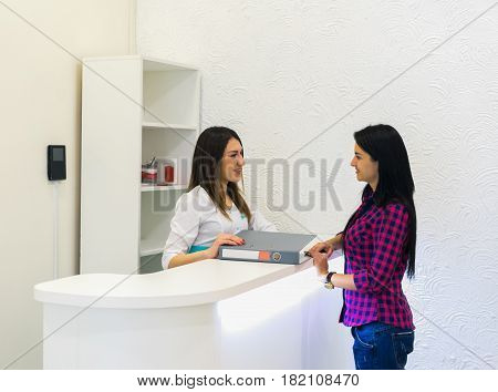 receptionist at medical clinic with patient holding logbook