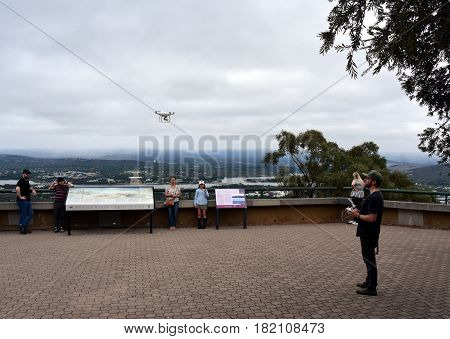 Canberra Australia - March 19 2017. A guy playing with a white drone at Mount Ainslie lookout.