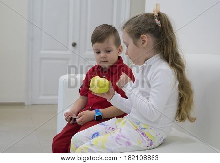 Small boy and girl sitting on the sofa and talking. Girl is holding green apple. Boy is looking at the apple.