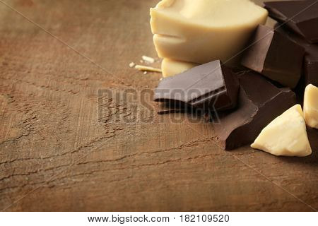 Pieces of dark and white chocolate on wooden background