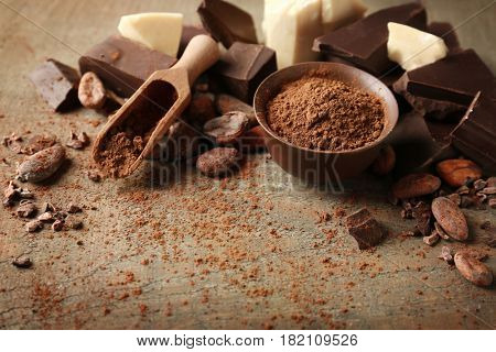 Composition with cocoa powder in bowl and beans on wooden background