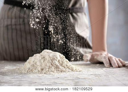 Woman making dough for ravioli on table
