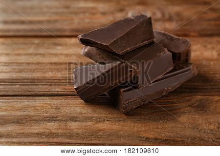 Pieces of dark chocolate on wooden background