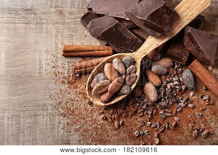 Spoon with cocoa beans and chocolate on wooden background