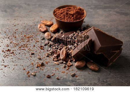 Composition with cocoa beans and pieces of chocolate on table