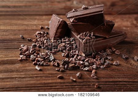 Pieces of dark chocolate and cocoa nibs on wooden background