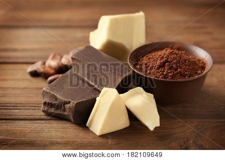 Pieces of different chocolate and bowl with cocoa powder on wooden background