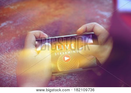 two hand holding smart phone with Live Streaming concert Live streaming word and microphone on screen mobile phone music online concept.