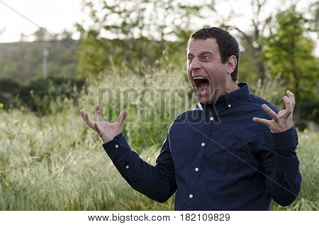 Man screaming in anger with hands out and mouth wide open.