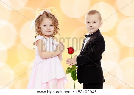Little boy in black suit with bow tie gives a big red rose charming little girl.Brown festive, Christmas background with white snowflakes, circles.