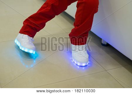 Small boy wearing glowing white led sneakers. Shoes with light.