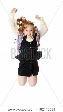 Joyful girl schoolgirl in black dress and white shirt and a knapsack on his shoulders. She jumps, hands up.Isolated on white background.