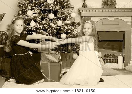 Cute little twin girls, sitting on the floor near the Christmas tree and electric fireplace on which candles are burning. In the hands of the girls boxes with gifts.Black-and-white photo. Retro style.