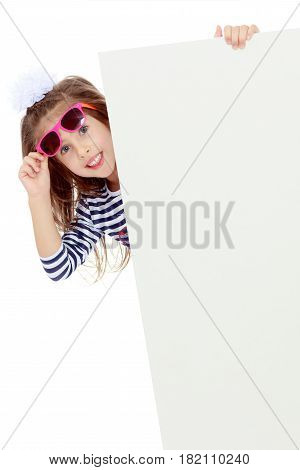 The little blonde girl with long hair and with a white bow on her head , in a blue striped summer dress.The girl in the dark sunglasses peeking from behind the banner.Isolated on white background.