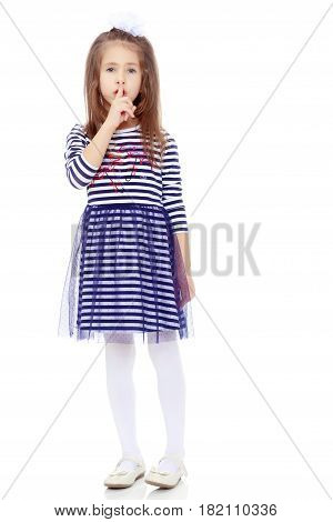 Beautiful little girl long hair and white bow on her head , in a summer dress in stripes.She holds an index finger around the lips. The gesture quiet.Isolated on white background.
