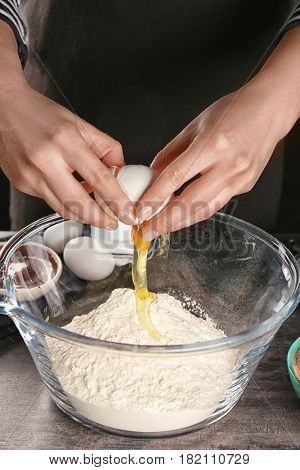 Woman preparing dough for cocoa brownies on table