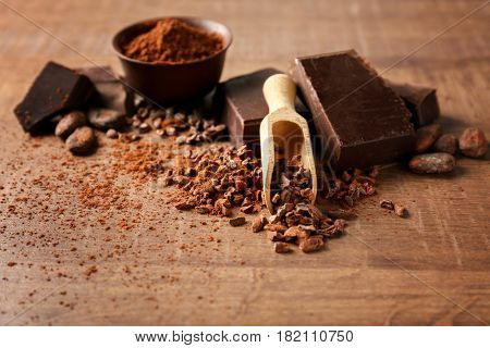 Scoop with aromatic cocoa nibs and pieces of chocolate on wooden background