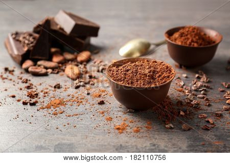 Bowl with aromatic cocoa powder and pieces of chocolate on table