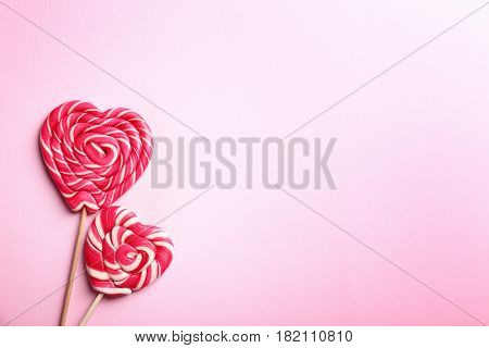 Tasty lollipops on color background
