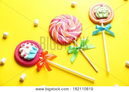 Tasty lollipops on color background