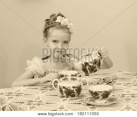 Beautiful little girl Princess , sitting at an antique table with a lace tablecloth and drinking tea.She pours in a Cup of boiling water from the kettle.Black-and-white photo. Retro style.