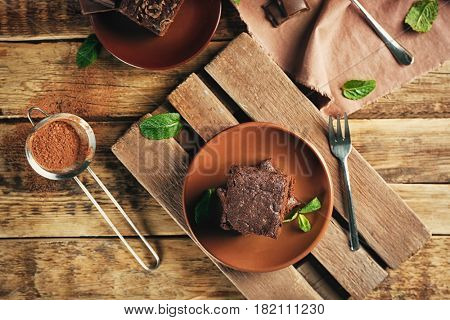 Plate with delicious cocoa brownies on wooden table