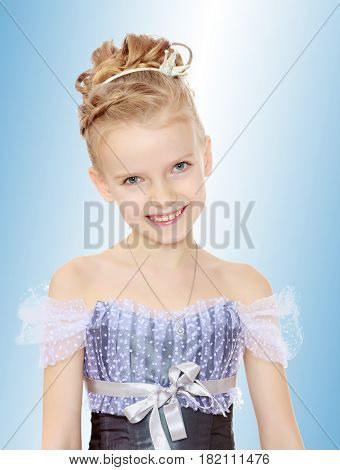 Slender little girl , with beautiful hair on his head, elegant long Princess dress.Girl smiling at the camera. Close-up.On the pale blue background.