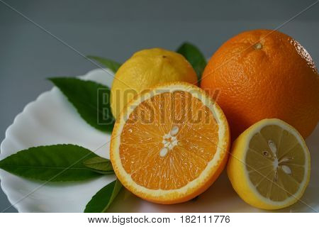 Organic orange and lemon on white plate with the gray background - Isolated