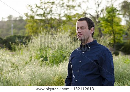 Optimistic man outdoors in a grassy field thinking of what tomorrow will bring.