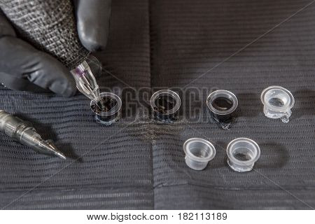 Tattoo artist refilling pen from ink poured into small cups. Closeup