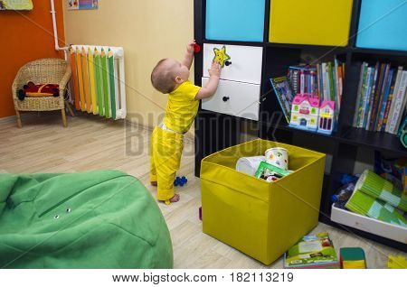 A small child plays with toys in the children's room pasted to the closet