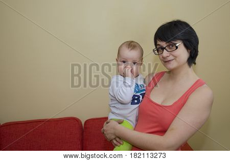 Young mother with glasses holds a small child in her arms
