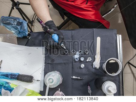 Tattoo artist table while she is refilling the gun. Overhead shot