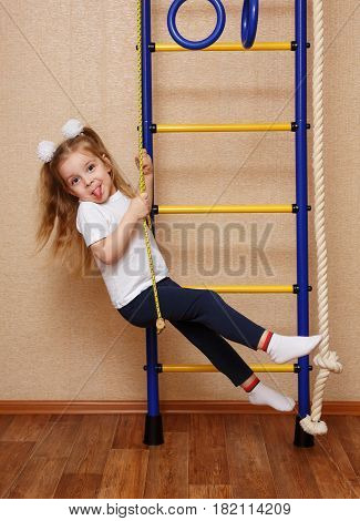 Little girl in sportswear showing tongue and riding on a swing on the wall bars. The concept of a healthy lifestyle from a young age. Children's sports.