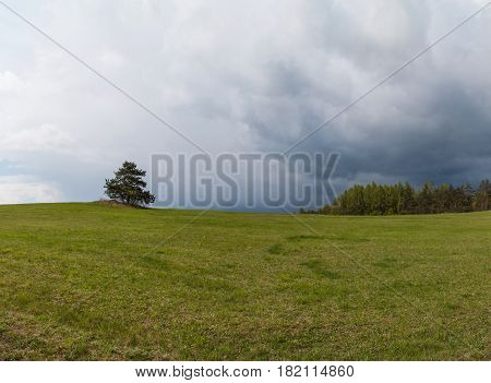 Spring rainy day in pastures in the Czech Republic. Overcast day. Panorama meadows