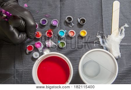 Tattoo artist refilling the pen with red ink. Overhead shot