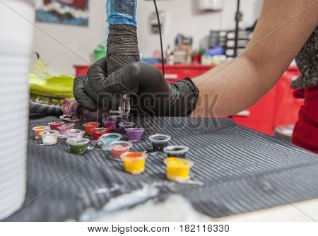 Tattoo artist refilling pen from ink cup. Closeup