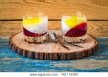 Color jelly in transparent glass  on rustic wooden surface